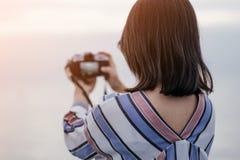 Les jeunes femmes tenant le seul appareil-photo de prise prennent la photo avec le backg de mer photos stock