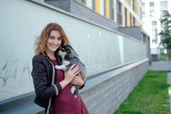 Les jeunes femmes tient son petit chiot d'animal familier de meilleur ami de chien de traîneau dans des ses bras Amour pour des c Photographie stock libre de droits