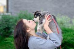 Les jeunes femmes tient son petit chiot d'animal familier de meilleur ami de chien de traîneau dans des ses bras Amour pour des c Images libres de droits