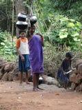 Les jeunes filles apprennent à porter des bacs de l'eau Photographie stock