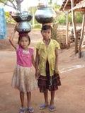 Les jeunes filles apprennent comment porter l'eau dans des bacs Photos libres de droits