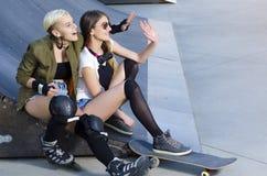 Les jeunes filles dans le patin se garent avec les raies de rouleau et le panneau de patin Photo stock