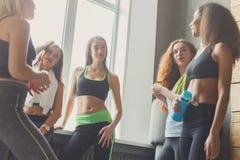 Les jeunes filles dans les vêtements de sport causant avant yoga classent Photo stock