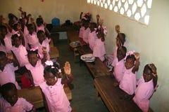 Les jeunes filles et garçons haïtiens d'école de jardin d'enfants montrent des bracelets d'amitié dans le village Image libre de droits