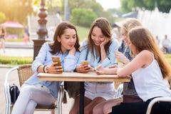Les jeunes filles heureuses d'étudiant utilisent des smartphones dans le parc photo stock