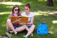 Les jeunes filles s'asseyant sur l'herbe en parc et se prépare aux classes, porte les vêtements sport et les lunettes de soleil,  images stock