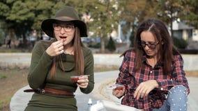 Les jeunes filles s'asseyent en parc en automne, elles mangent des pommes frites et un sandwich, communiquent banque de vidéos