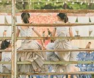 Les jeunes filles s'asseyent sur la tribune photographie stock