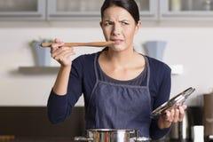 Les jeunes font cuire goûter sa nourriture avec une grimace images libres de droits