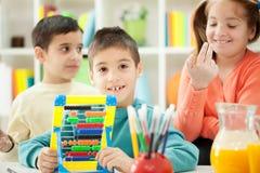 Les jeunes frères et les soeurs apprennent ensemble des maths sur l'abaque Images libres de droits