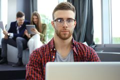 Les jeunes futés utilisent des instruments tout en travaillant dur dans le bureau moderne Jeune homme travaillant sur son ordinat Image stock