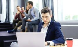 Les jeunes futés utilisent des instruments tout en travaillant dur dans le bureau moderne Jeune homme travaillant sur son ordinat Photos stock