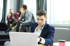 Les jeunes futés utilisent des instruments tout en travaillant dur dans le bureau moderne Jeune homme travaillant sur son ordinat Images stock