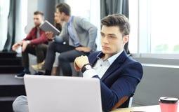 Les jeunes futés utilisent des instruments tout en travaillant dur dans le bureau moderne Jeune homme travaillant sur son ordinat Photo stock