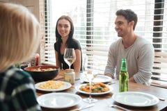 Les jeunes gais appréciant le repas tout en se reposant à la table dinning Photographie stock