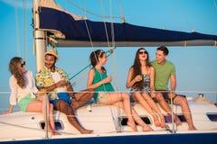 Les jeunes gais détendant sur un yacht Photographie stock