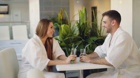 Les jeunes gais des verres de cocktail parlent, de font tinter et boivent tout en se reposant à la table dans la station thermale banque de vidéos