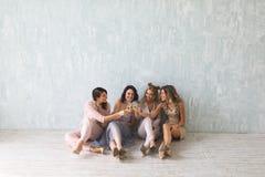 Les jeunes gais encourageant avec des cannelures de champagne et semblant heureux tout en ayant la partie à la maison Images libres de droits