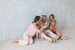 Les jeunes gais encourageant avec des cannelures de champagne et semblant heureux tout en ayant la partie à la maison Photographie stock