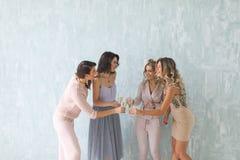 Les jeunes gais encourageant avec des cannelures de champagne et semblant heureux tout en ayant la partie à la maison Images stock