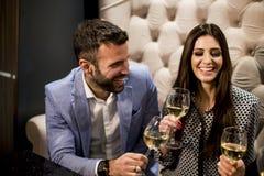 Les jeunes gais grillant avec du vin blanc Photo stock