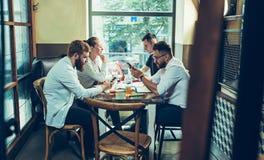 Les jeunes gais sourient et font des gestes tout en détendant dans le bar Image stock