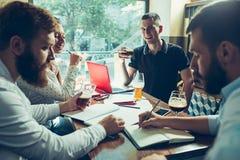 Les jeunes gais sourient et font des gestes tout en détendant dans le bar Images stock