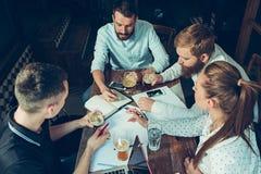 Les jeunes gais sourient et font des gestes tout en détendant dans le bar Photographie stock libre de droits
