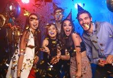 Les jeunes gais versés avec des confettis sur un club font la fête Photo stock