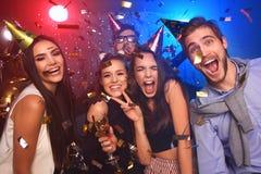 Les jeunes gais versés avec des confettis sur un club font la fête Image stock