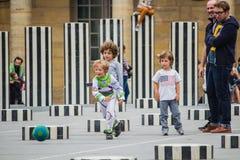 Les jeunes garçons jouent au football parmi Colonnes de Buren, Palais Roya Photo libre de droits
