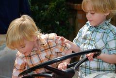 Les jeunes garçons jumeaux essayent d'orienter la roue surdimensionnée Photo libre de droits