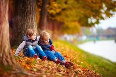 Les jeunes garçons, meilleurs amis s'asseyant sous l'arbre en automne se garent Photographie stock