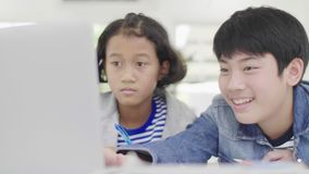 Les jeunes gar?ons utilisent des ordinateurs pour enseigner et expliquer le travail Aux amis avec des expressions du visage et de clips vidéos