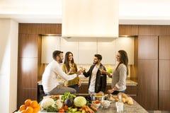 Les jeunes grillant avec du vin blanc dans la cuisine Photo libre de droits