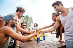 Les jeunes heureux avec de la bière célébrant ensemble dehors Photographie stock