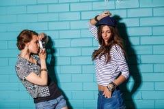 Les jeunes heureux avec l'appareil-photo de photo ayant l'amusement devant le bleu Photo libre de droits