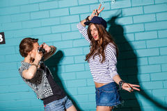 Les jeunes heureux avec l'appareil-photo de photo ayant l'amusement devant le bleu Image libre de droits