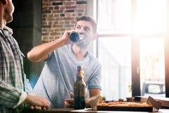 Les jeunes heureux ayant l'amusement avec de la bière et la pizza à la maison Images libres de droits