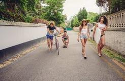 Les jeunes heureux ayant l'amusement avec la planche à roulettes et la bicyclette Photos libres de droits