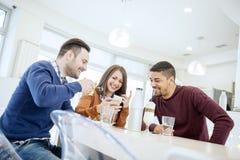 Les jeunes heureux ayant l'amusement dans un café Photo libre de droits