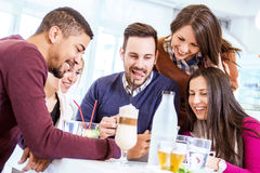 Les jeunes heureux ayant l'amusement dans un café Image libre de droits