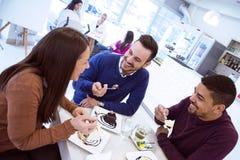 Les jeunes heureux ayant l'amusement dans un café, mangeant le gâteau Image stock