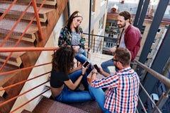 Les jeunes heureux ayant l'amusement sur des escaliers Photos libres de droits