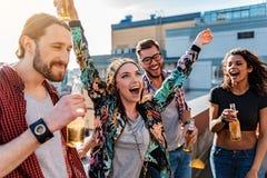 Les jeunes heureux ayant l'amusement sur la terrasse de dessus de toit Photo libre de droits