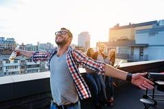 Les jeunes heureux ayant l'amusement sur la terrasse de dessus de toit Image stock