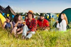 Les jeunes heureux buvant ensemble au terrain de camping Image libre de droits
