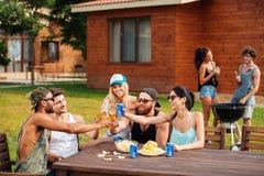 Les jeunes heureux célébrant et buvant dehors Photo libre de droits