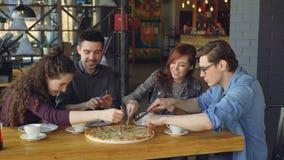 Les jeunes heureux coupent la grande pizza avec des couteaux, parlent et rient tout en dinant en café confortable Style de vie mo clips vidéos