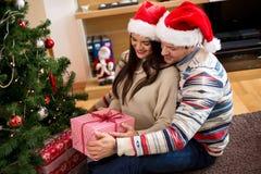 Les jeunes heureux donnent des cadeaux par l'arbre de Noël photo libre de droits